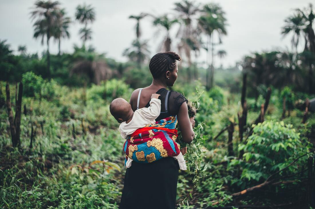 Woman with baby on her back in a field